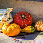 A gargoyle protecting pumpkins and gourds