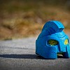 A blue toy on the sidewalk. The toy is about the size of a tennis ball.