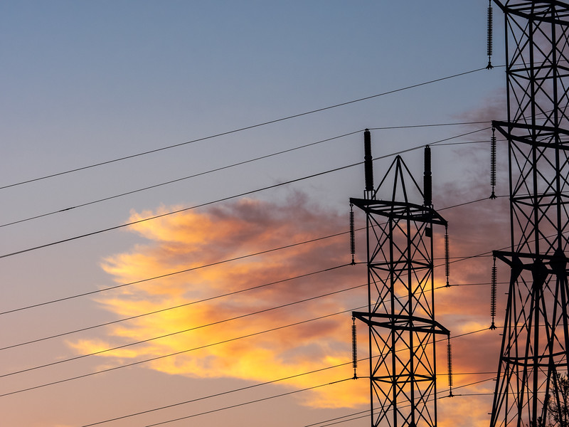 Transmission Towers and Sunset-Colored Clouds