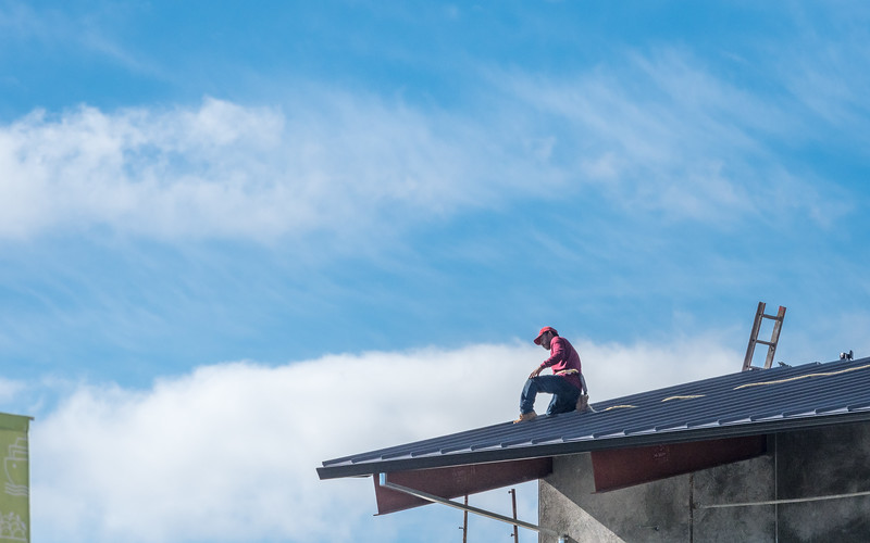 Man Working on Roof and Clouds