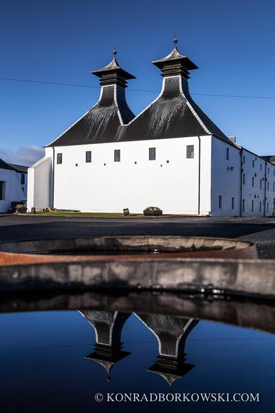 Pagodas reflection in a whisky barrel, Ardbeg Distillery, Isle of Islay.