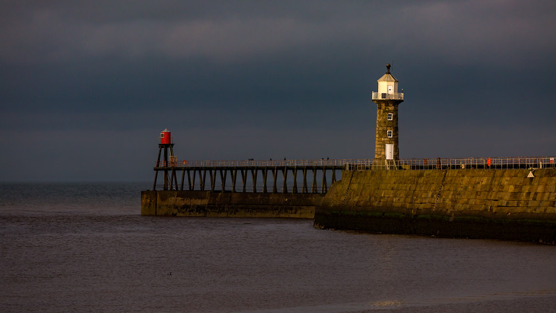 After a gray day at Whitby the sun made a brief visit before slipping behind the hillside, leaving me with this moody picture of the east pier of the harbour