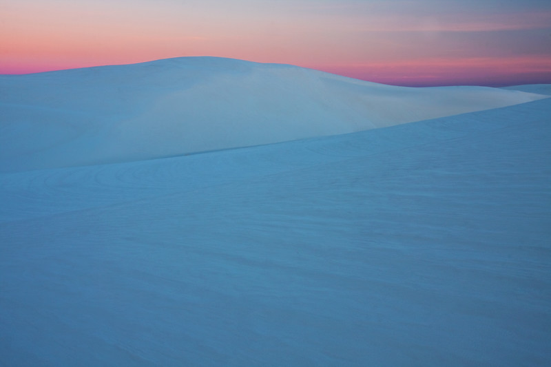 One of my favorite pictures from the trip....sunrise at the White Sands on New Years day 2010. It was actually a bit complicated to get this photo, but glad I went through the effort. First hurdle, the park doesn't open the gates until 7am, which is too late to be in the right spot for sunrise. So, I worked out a deal with the park rangers the day prior to open the gates an hour early just for me (amazing what $50 will buy!)....I arrive at 5:45am, and am feeling pretty good that I have the park all to myself! Into the park, and trekking out on the dunes. At 19 degrees, I'm feeling pretty stupid for the way I dressed. My excitement quickly fades, as my hands and ears turn numb. After about a 20 minute walk, I look around and think...it would be really easy to get lost in this place! Sure hope I can find my way back to the car. The wind is howling, and the light minimal as I wait for sun to rise. My attempts at photos prior to sunrise just up the frustration level as I can't accomplish what's in my head with the blue moonset. I start feeling like a complete rookie photographer, and wondering why the hell I paid money to freeze my butt off in the desert. Then the sun begins to rise in the East....I find a spot with some cool patterns in the sand and a nice untouched dune and setup the tripod. Only a few minutes of good light, better thaw out my fingers in a hurry! Setup tripod, meter, focus, shutter, apeture, all good. Freezing cold, but happy with the result.