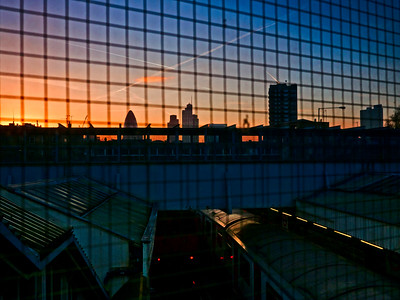 2011, January, a view from inside the wooden platform bridge towards the City of London skyline, at dusk. You can see a District Line train at rest on the inner platforms (which have now been removed).