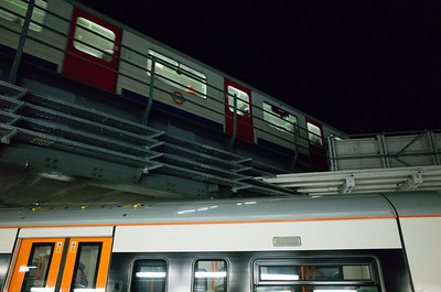 2013, November, a view of an Underground train on the line above a waiting Overground train below it.