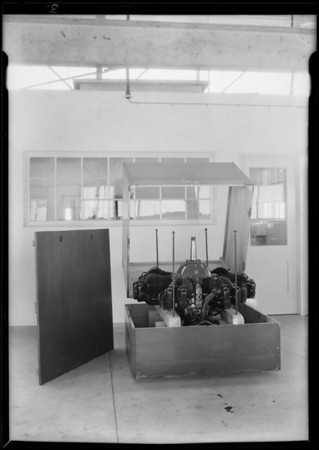 Packing motor into box, tool kit, man working on crankshaft, Southern California, 1929