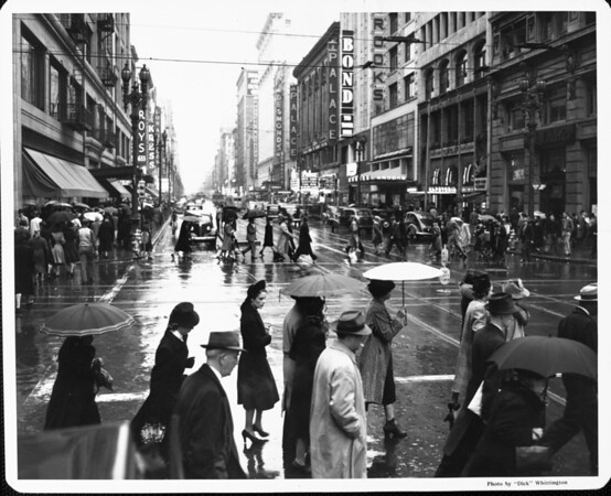 Pedestrians crowd the crosswalks of Downtown on a rainy day