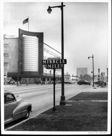 A view of the Miracle Mile sign with the May Company in the background