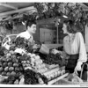 A woman wearing a palm tree brooch is being assisted by a man working at the produce stand at the Farmers Market