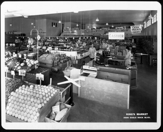 The interior of King's Market showing the cashier, produce section, and advertisements such as a 22-ounce bottle of root beer for 5 cents