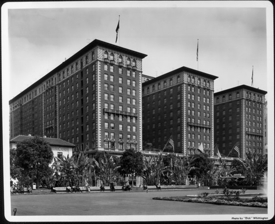 "The Biltmore Hotel as seen from Pershing Square, with men sitting on the park benches, some of which are ""reserved for women and children only"""