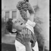 Joe with a bunch of grapes, Southern California, 1925