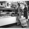 Two women with a wicker shopping cart buying meat from the butcher at the Farmers Market