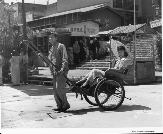 A man pulling a woman sitting on a chariot smile for the camera in Chinatown