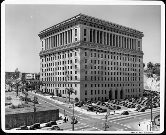 "A view of the Hall of Justice showing its parking lot and a billboard stating that Prohibition is ""the best method against liquor traffic"""