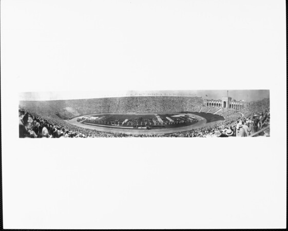A panoramic view of the Los Angeles Memorial Coliseum with a capacity crowd and the marching band performing on the field