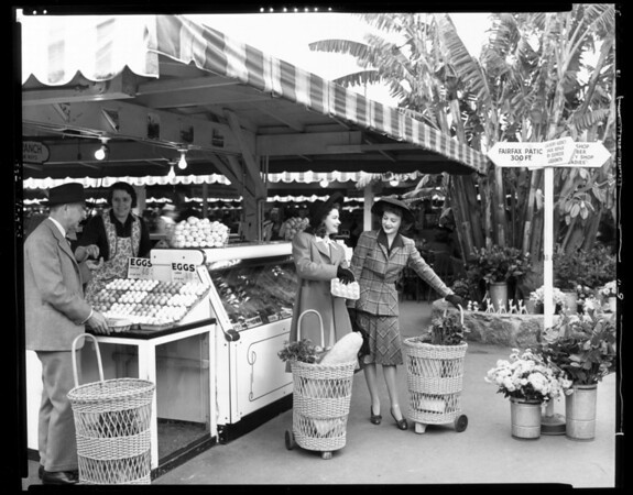 A man gets his change from the woman working at the egg counter at the outdoor Farmers Market, while two young women with wicker shopping carts stand nearby