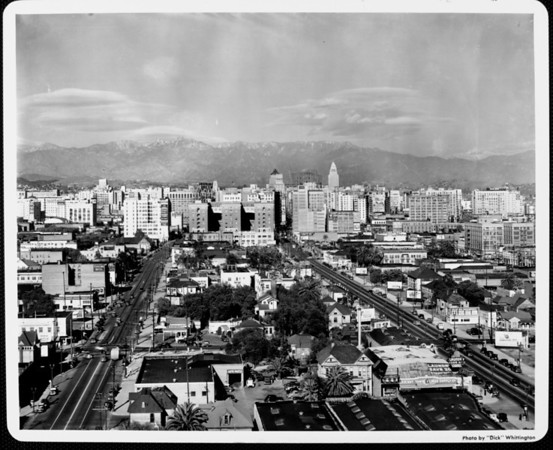 Looking northeast along Broadway and Hill Street, with City Hall and the San Gabriel Mountains in the distance