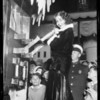 Nancy Carroll at switchboard turning on Christmas street light, Southern California, 1929