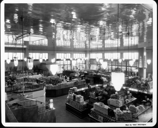 The interior of a grocery store before it opens showing the merchandise in display cases and people looking in through the windows