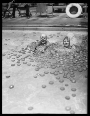Ambassador plunge, girls swimming in pool of oranges, Los Angeles, CA, 1929