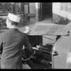 Man putting oil in car, Southern California, 1931
