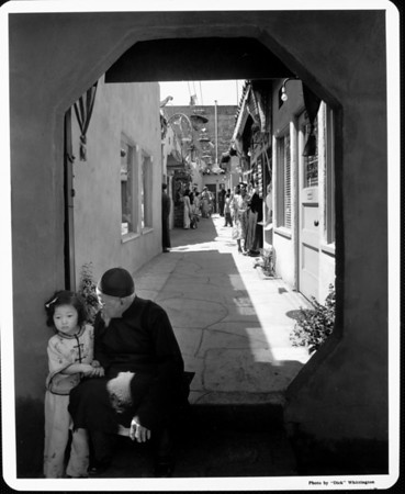 An old man sitting with a young girl in a doorway which leads to many residences in Chinatown