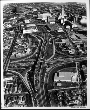 An aerial view of downtown Los Angeles, looking southeast over the intersection of the I-101 and I-110 Freeways toward City Hall and Union Station, 1964
