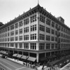 A high-angle view of the May Company Building with people walking along the sidewalk on the corner of Eighth Street and Broadway