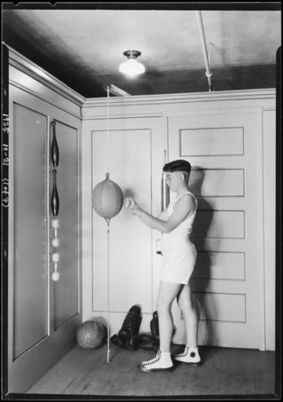 Boy at punching bag, Christmas topics, Broadway Department Store, Los Angeles, CA, 1925