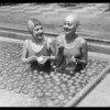 Ambassador plunge, girls swimming in pool of oranges, Los Angeles, CA, 1929
