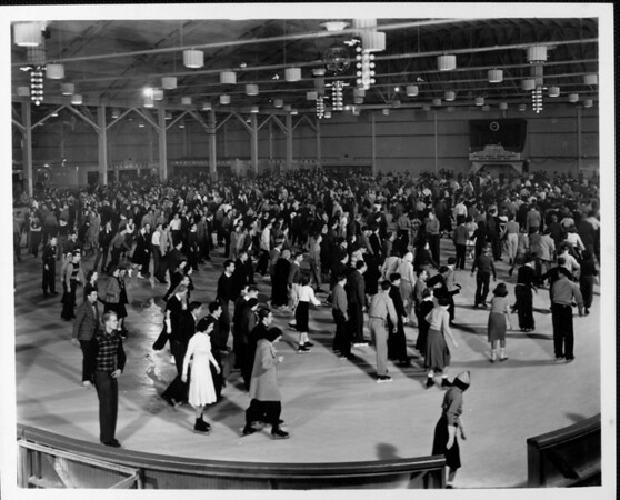 A crowded skating rink with a sign announcing a couples contest on Monday nights and races on Wednesday night