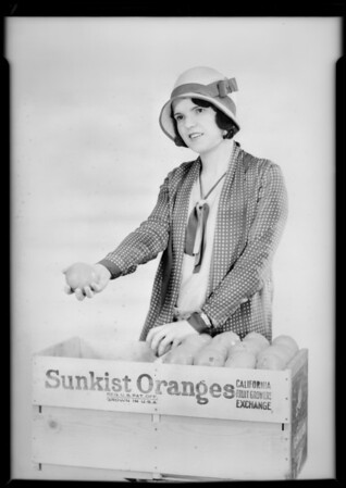 Girl passing out Sunkist oranges, Southern California, 1929