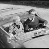 Couple speeding in open roadster, Southern California, 1931