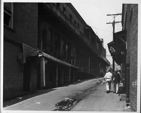 Two men walking through alley