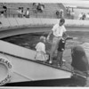 A Marineland performance featuring a girl and boy feeding whale with the help of a trainer