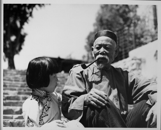 Chinatown, old Chinese man with pipe speaking with young Chinese girl, Chinese costumes