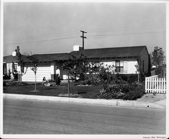 Residential home with couple in front yard