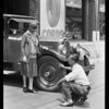 Tire changing on car of Mrs. Reed, Southern California, 1929