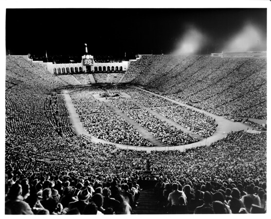A religious service taking place at night in the Coliseum at Exposition Park