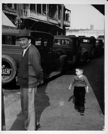 Parked cars and trucks, and an old man and young boy on the street in Chinatown