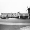 Palm Market with a windmill and as part of a strip mall, radio shop, flower shop, Palm Drug Company, cafe, meats, Van de Kamps bakery
