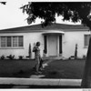 Residential home with woman and dog in front yard