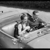 Couple speeding in open roadster, Southern California, 1931