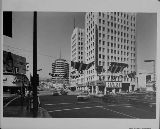 A street level shot of the corner at Hollywood Boulevard and Vine Street in Hollywood, showing American Airlines, Capitol Records, Hody's Restaurant, and E.F. Hutton, ca.1955-1965
