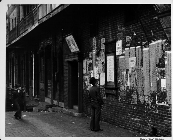 Men looking at wall of posters, posted bills in Chinatown