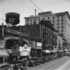 Main Street, looking north between Second Street and Third Street, Mobil Gas / Mobiloil, Higgins Building, Arrow Theatre, Uncle John's Store, 243 South Main Street