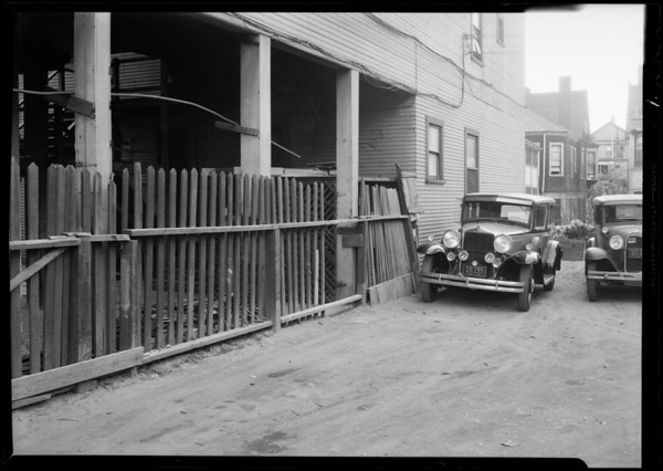 Hole in fence rear of Cumbert and hotel, Southern California, 1931