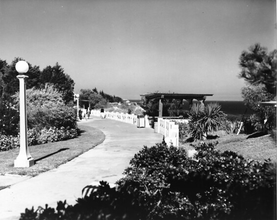 A walkway in a park overlooking the ocean