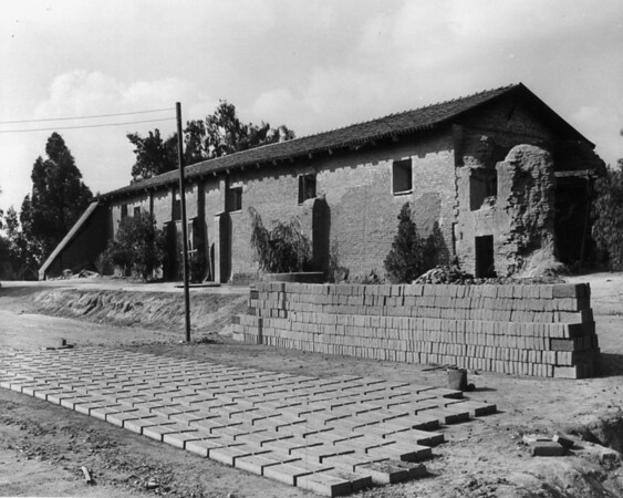 Adobe bricks to be used in the restoration of the San Fernando Mission are stacked in front of a damaged building